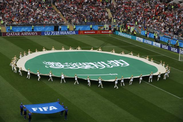 Volunteers hold the flag of Saudi Arabia ahead of the group A match between Russia and Saudi Arabia which opens the 2018 soccer World Cup at the Luzhniki stadium in Moscow, Russia, Thursday, June 14, 2018. (AP Photo/Darko Bandic)