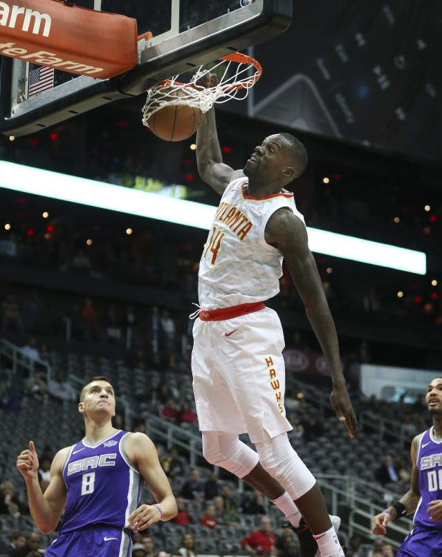 Atlanta Hawks center Dewayne Dedmon (14) scores as Sacramento Kings guard Bogdan Bogdanovic (8) looks on during the first half of an NBA basketball game Wednesday, Nov. 15, 2017, in Atlanta. (AP Photo/John Bazemore)