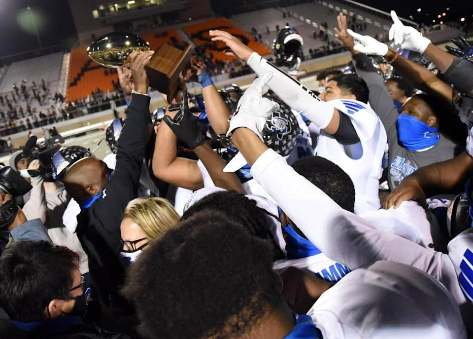 Mansfield Summit's Coach Channon Hall, left holds the trophy as he and his team celebrate their 34-31 win over Colleyville Heritage in their Division 1-5A Regional Round Play-off football game Saturday, December 26, 2020 at Bearcat Stadium in Aledo, Texas. Special/Bob Haynes