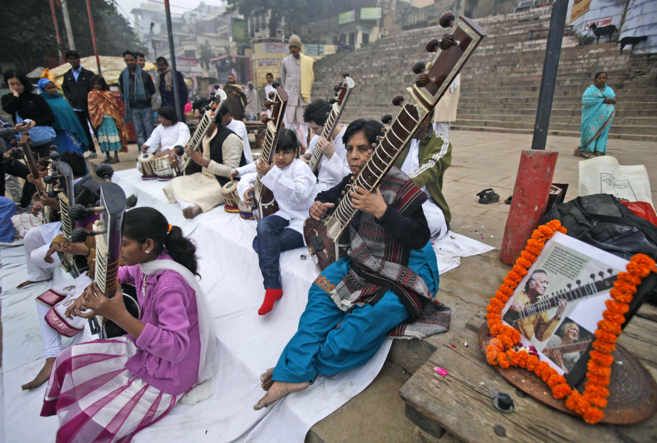Members of Vande Mataram music society play sitars during a function to offer tributes to the late legendary Indian sitar player Ravi Shankar on the banks of the Ganges River in Varanas , India, Thursday, Dec. 13, 2012. Shankar, who is credited with connecting the world to Indian music, died Tuesday in San Diego at the age of 92. (AP Photo/Rajesh Kumar Singh)