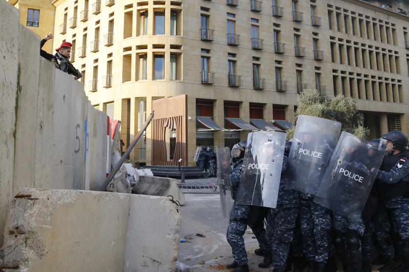 An anti-government demonstrator throws stones toward riot police on a road leading to the parliament building, during a protest against a parliament session to vote of confidence for the new government, in downtown Beirut, Lebanon, Tuesday, Feb. 11, 2020. (AP Photo/Bilal Hussein)