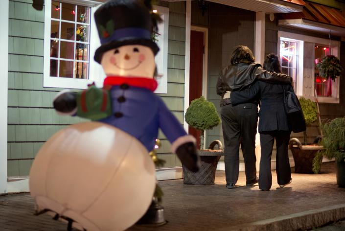 FILE - In this Dec. 19, 2012 file photo, mourners walk past a Frosty the Snowman Christmas decoration after visiting a memorial for the Sandy Hook Elementary School shooting victims, in Newtown, Conn. In the wake of the shooting, the grieving town is trying to find meaning in Christmas. (AP Photo/David Goldman, File)