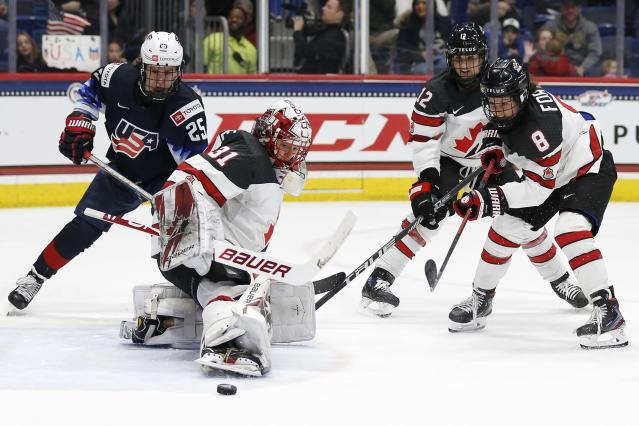 Canada's Geneviève Lacasse (31) deflects the puck in front of United States' Alex Carpenter (25) during the third period of a rivalry series women's hockey game in Hartford, Conn., Saturday, Dec. 14, 2019. (AP Photo/Michael Dwyer)