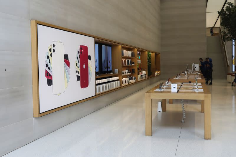 FILE PHOTO: Staff stand in an Apple store with no customers after it was closed on Regents Street in London
