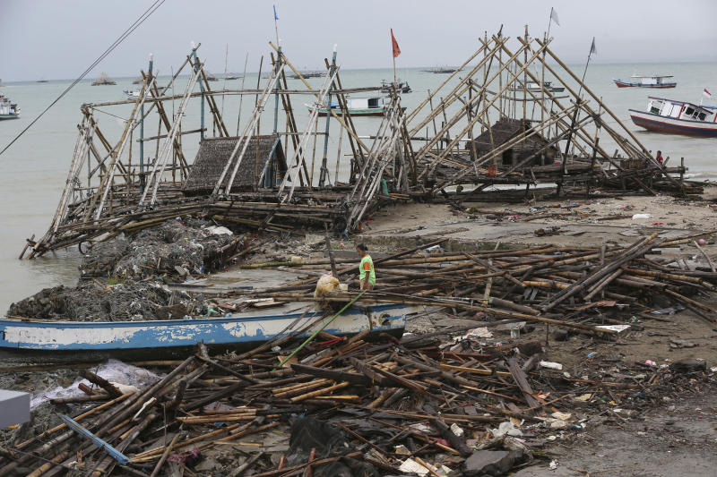 A woman walks amid debris at a tsunami-ravaged village in Sumur, Indonesia, Tuesday, Dec. 25, 2018. The Christmas holiday was somber with prayers for tsunami victims in the Indonesian region hit by waves that struck without warning Saturday night.(AP Photo/Tatan Syuflana)