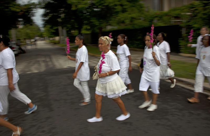 Members of Cuba's Ladies in White dissident group participate in a march marking one year since the death of a co-founder of the group, Laura Pollan, in Havana, Cuba, Sunday, Oct 14, 2012. The Ladies in White was formed in 2003 mostly by wives and family members of 75 dissidents jailed in a crackdown on dissent. Pollan had been married to one of the dissident prisoners, Hector Maseda. (AP Photo/Ramon Espinosa)