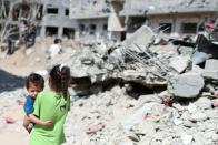 A Palestinian girl carries a boy amid the rubble of their houses destroyed by Israeli air strikes