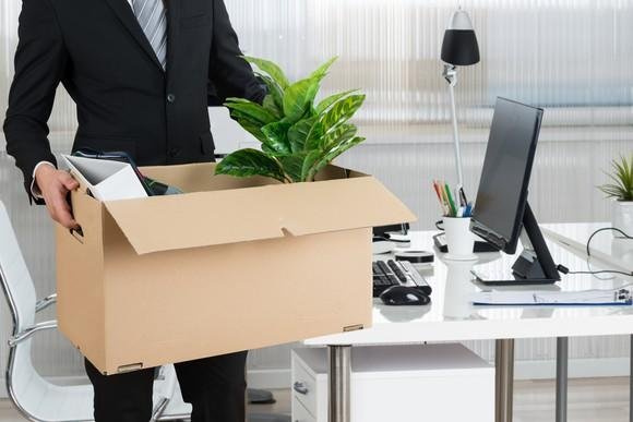 A man carries his belongings from an office in a cardboard box.