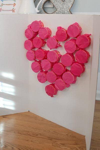 """<p> Fill paper cups with dollar-store treats, cover them with tissue paper, attach them to poster board in a heart shape then let kids take turns """"breaking"""" the heart to claim their prizes. Little ones will have so much fun bursting through the tissue paper — it's like a personal piñata for every child. </p><p><em><a href=""""https://balancinghome.com/my-heart-is-bursting-a-valentine-classroom-activity/"""" rel=""""nofollow noopener"""" target=""""_blank"""" data-ylk=""""slk:Get the tutorial at Balancing Home »"""" class=""""link rapid-noclick-resp"""">Get the tutorial at Balancing Home »</a></em><br></p>"""