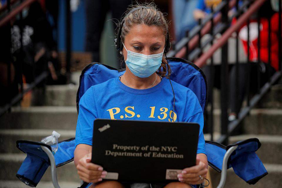 A teacher works outside a school building for safety reasons, as preparations begin for the delayed start of the school year, following the outbreak of the coronavirus disease (COVID-19) in the Brooklyn borough of New York City, U.S., September 14, 2020. (PHOTO: REUTERS/Brendan McDermid)