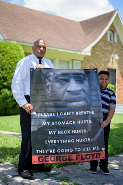 George Floyd's childhood friend Mallory Jackson and his son Mikhail Jackson pose with a poster in honor of the man killed by police on May 25 (AFP Photo/Mark Felix)