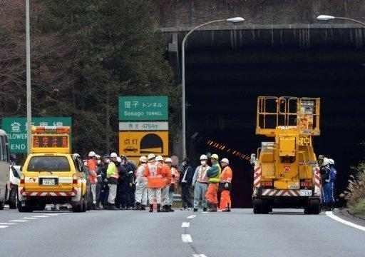 Rescue workers and policeman gather on the road leading into the collapsed Sasago tunnel. Japanese rescuers found five charred bodies and a trucker was pronounced dead after being pulled from his vehicle following the collapse