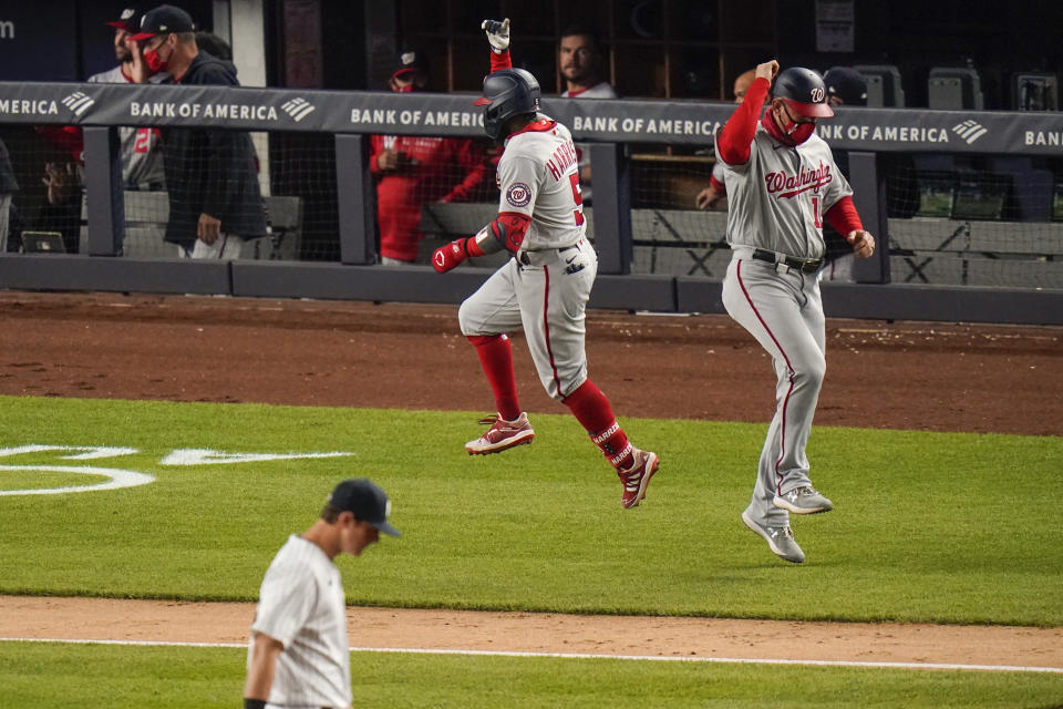 Washington Nationals' Josh Harrison (5) celebrates with third base coach Bob Henley after hitting a three-run home run during the eighth inning of the team's baseball game against the New York Yankees on Friday, May 7, 2021, in New York. (AP Photo/Frank Franklin II)