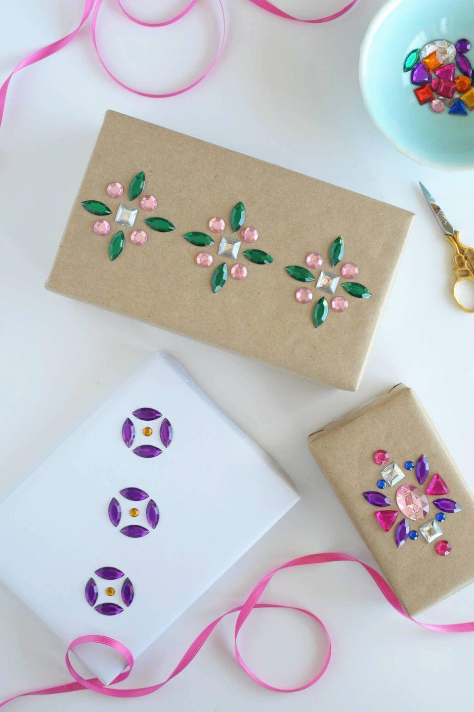 """<p>Make pretty patterns out of stick-on gemstones (or use a little craft glue for extra reinforcement!). For Christmas, you could even arrange them to look like ornaments. </p><p>Get the tutorial at <a href=""""https://www.aliceandlois.com/diy-rhinestone-gift-wrap/"""" rel=""""nofollow noopener"""" target=""""_blank"""" data-ylk=""""slk:Alice and Lois"""" class=""""link rapid-noclick-resp"""">Alice and Lois</a>.</p><p><a class=""""link rapid-noclick-resp"""" href=""""https://www.amazon.com/DoTebpa-Colorful-Rhinestone-Scrapbooking-Embellishments/dp/B074LRWLNS/?tag=syn-yahoo-20&ascsubtag=%5Bartid%7C10072.g.34015639%5Bsrc%7Cyahoo-us"""" rel=""""nofollow noopener"""" target=""""_blank"""" data-ylk=""""slk:SHOP RHINESTONES"""">SHOP RHINESTONES</a> </p>"""
