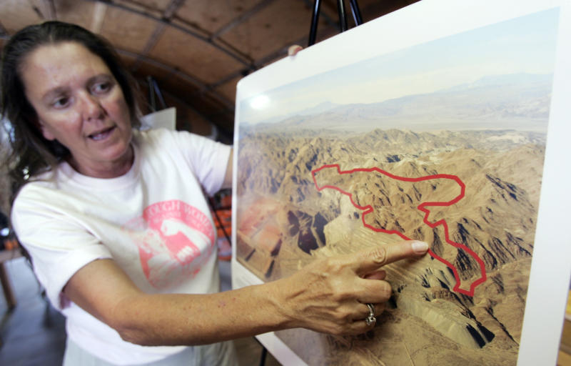 FILE - In an Oct. 6, 2006 file photo, Donna Charpied points to an area of a proposed dump site near Southern California's Joshua Tree National Park, at her home in Desert Center, Calif. Los Angeles County's sanitation districts are no longer pursuing plans to build a 4,000-acre landfill near Joshua Tree National Park on former mine land. David Rothbart, supervising engineer at the Sanitation Districts of Los Angeles County, said Friday, May 24, 2013 that the agency will use the $41 million set aside for the land purchase for more recycling and other projects. (AP Photo/Reed Saxon, File)