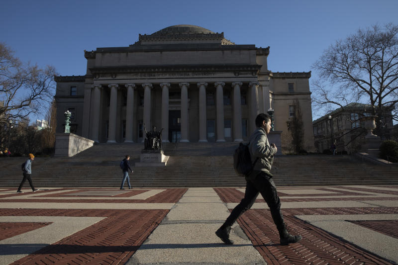 A man walks past Low Library on the Columbia University campus, Monday, March 9, 2020, in New York. Colleges nationwide are shutting down campuses with plans to continue instruction online, leaving some students distressed over where to go and professors puzzling over how to keep up higher education as they know it in the time of coronavirus. Dozens of colleges have canceled in-person classes temporarily or the balance of the semester. (AP Photo/Mark Lennihan)