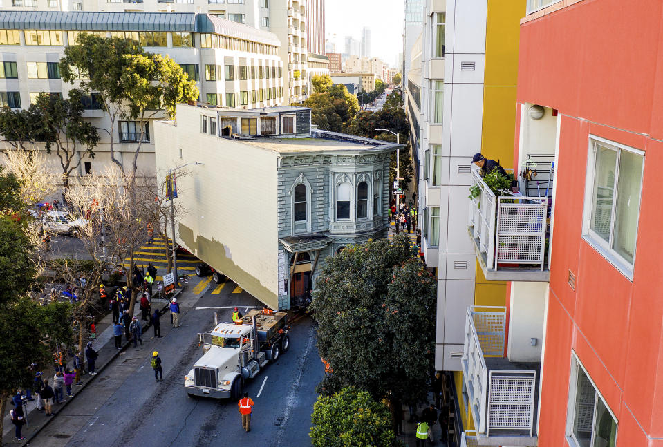 A man watches from a balcony as a truck pulls a Victorian home through San Francisco on Sunday, Feb. 21, 2021. The house, built in 1882, was moved to a new location about six blocks away to make room for a condominium development. According to the consultant overseeing the project, the move cost approximately $200,000 and involved removing street lights, parking meters, and utility lines. (AP Photo/Noah Berger)