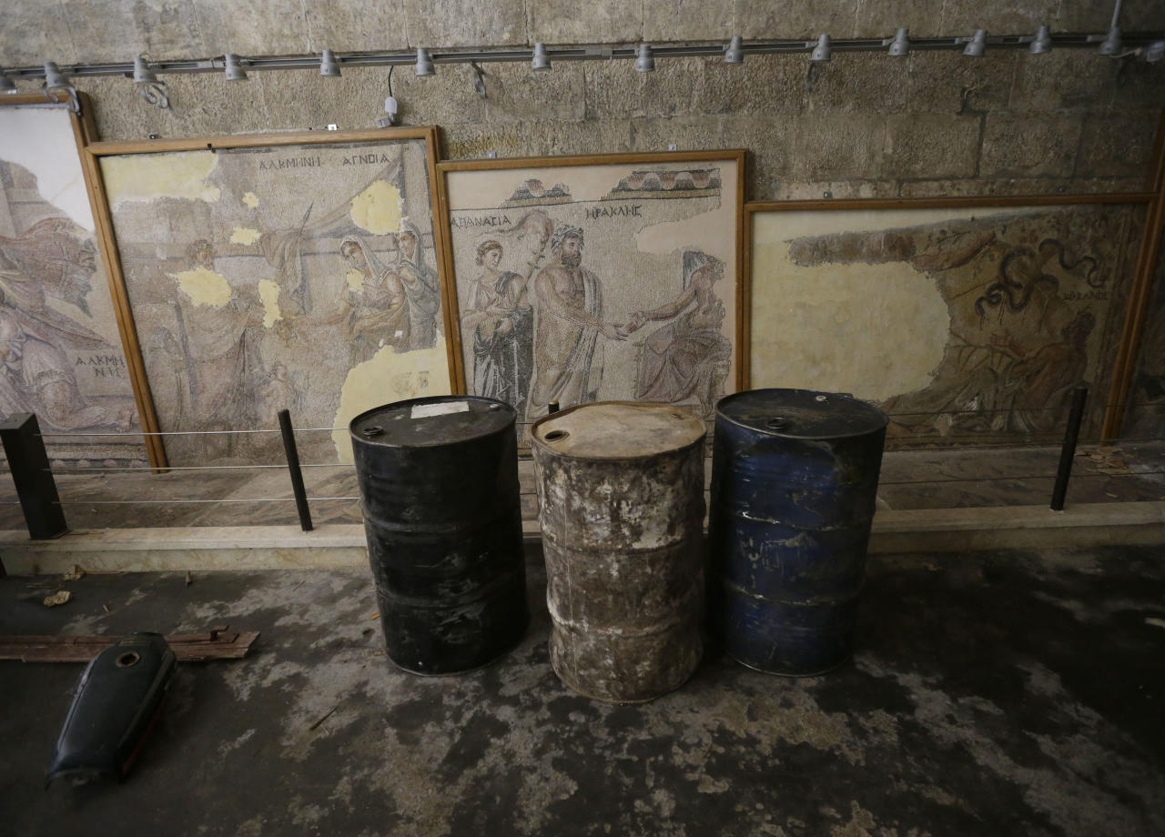 In this photo taken Tuesday, Feb. 26, 2013, fuel barrels are stored in front of Roman and Byzantine mosaics inside the 17th-century caravanserai, which presently serves as a headquarters for the Free Syrian Army, in Maaret al-Numan, Idlib province, Syria. Across northern Syria, rebels, soldiers and civilians are making use of the country's wealth of ancient and medieval remains for protection. The structures are built of thick stone that has already withstood the ravages of centuries. They are often located in strategic spots overlooking towns and roads. (AP Photo/Hussein Malla)