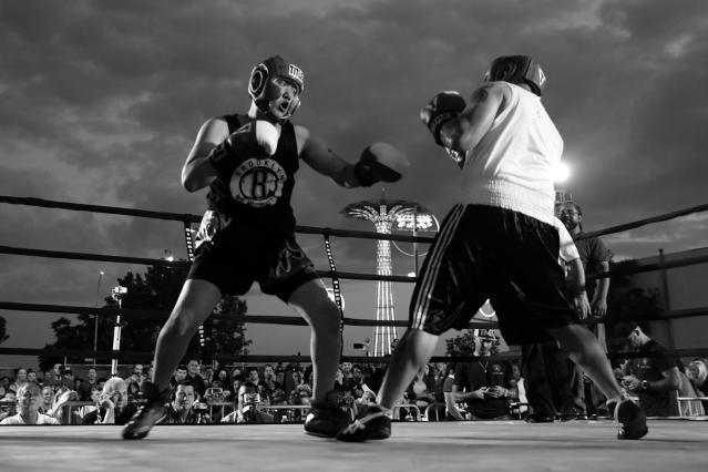 <p>Port Authority Police officers Jin Ha and Adam Pollack settle a dispute in the ring during a grudge match at the Brooklyn Smoker in the parking lot of Gargiulo's Italian restaurant in Coney Island, Brooklyn, on Aug. 24, 2017. (Photo: Gordon Donovan/Yahoo News) </p>