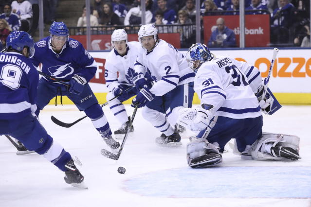Toronto Maple Leafs goaltender Frederik Andersen (31) keeps an eye on the puck before it is shot in by Tampa Bay Lightning center Tyler Johnson (9) during second-period NHL hockey game action in Toronto, Monday, March 11, 2019. (Cole Burston/The Canadian Press via AP)