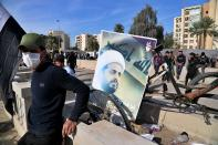 FILE - In this Jan. 1, 2020 file photo, a supporter of pro-Iranian militiamen stands by a poster of Qais al-Khazali, the leader of the militant Shiite group Asaib Ahl al-Haq, or League of the Righteous, during a sit-in in front of the U.S. embassy in Baghdad, Iraq. On Friday, Nov. 20, two Iraqi officials say Iran has instructed allies in the Middle East to be on high alert and avoid provoking tensions with the U.S. that could give an outgoing Trump Administration cause to launch attacks in his final weeks in office. (AP Photo/Khalid Mohammed, File)