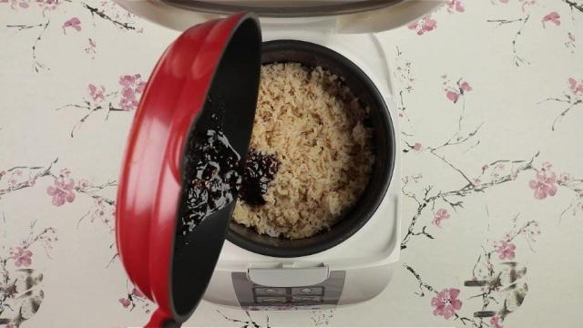 Pouring sauce from frying pan into brown rice in rice cooker