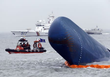"""Rescue boats sail around the South Korean passenger ship """"Sewol"""" which sank, during their rescue operation in the sea off Jindo, in this April 17, 2014 file photograph. REUTERS/Kim Kyung-Hoon"""