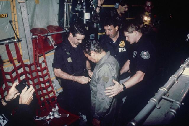 <p>Manuel Noriega watches as U.S. Drug Enforcement Agents place chains around his waist aboard a C-130 transport plane, Jan. 4, 1990. (AP Photo) </p>