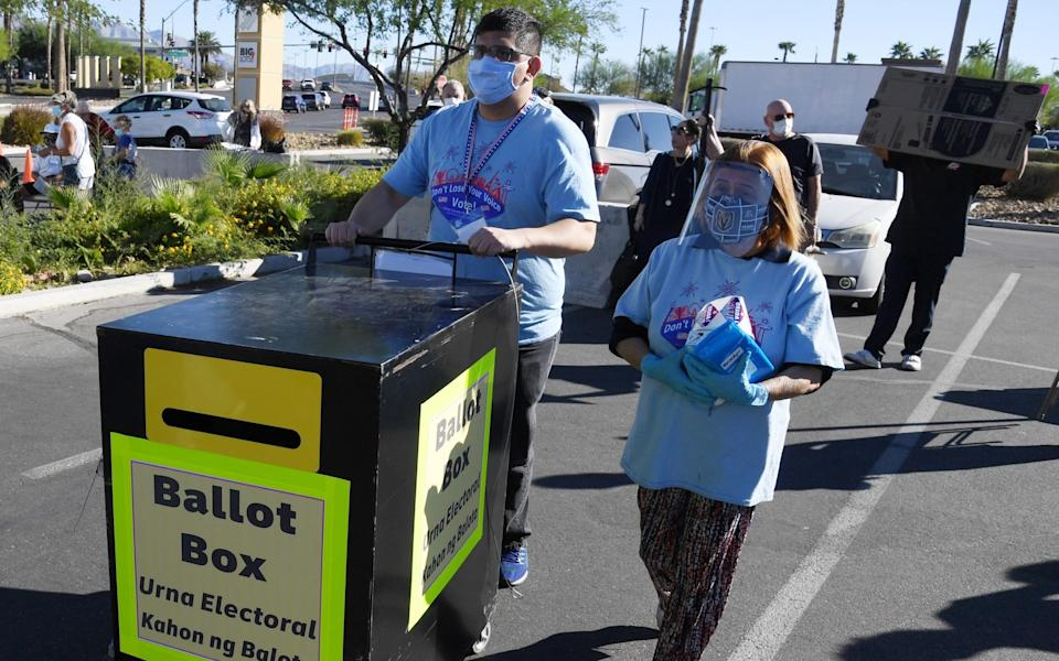 Workers place a ballot box for dropping off mail-in ballots next to a tent being used as an early voting polling location - Ethan Miller/Getty Images