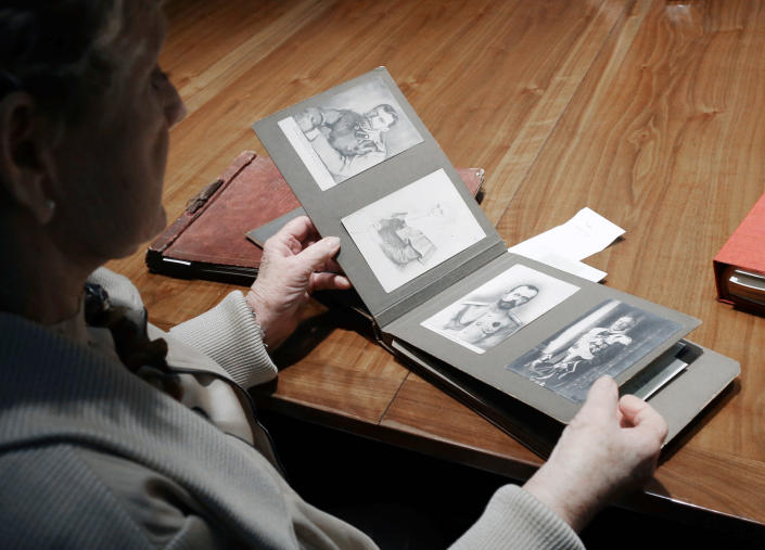 """Dorothy McFerrin looks through an old family photo album from Russian Czar Nicholas II Friday, Feb. 1, 2013, in Houston. McFerrin and her husband, Artie, own one of the largest private collections of authentic Faberge, the czar's personal jeweler, items in the United States. Featuring more than 350 objects, the exhibit """"Fabergé: A Brilliant Vision,"""" runs through Dec. 31, 2013 at the Houston Museum of Natural Science. (AP Photo/Pat Sullivan)"""