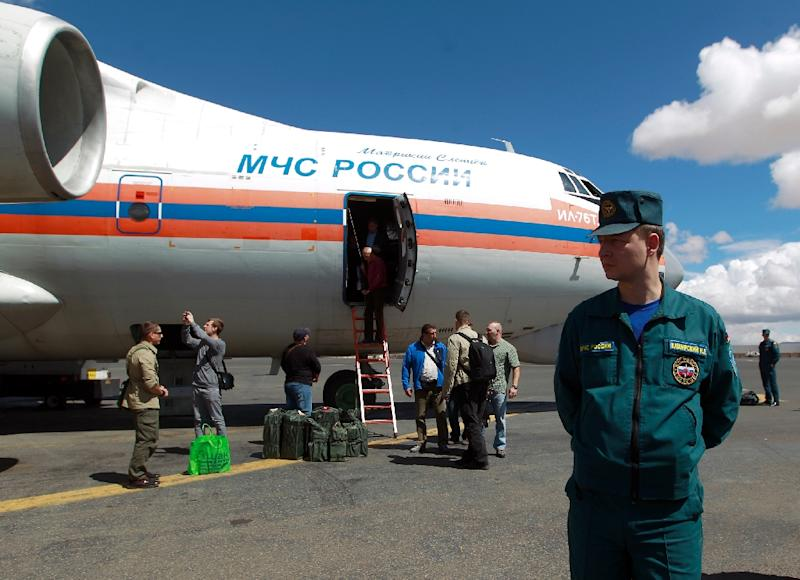 A Russian security guard stands near a plane that Moscow says is carrying 20 tonnes of aid, in the Yemeni capital Sanaa on November 5, 2015