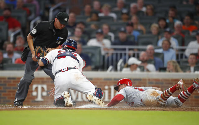 St. Louis Cardinals Kolten Wong is tagged out at home by Atlanta Braves catcher Kurt Suzuki (24) during the fifth inning of a baseball game, Tuesday, Sept. 18, 2018, in Atlanta. (AP Photo/Todd Kirkland)