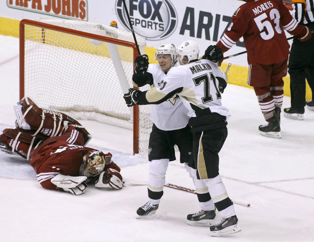 Pittsburgh Penguins' Evgeni Malkin (71), of Russia, celebrates with teammate Jussi Jokinen (36), of Finland, after Malkin's second period goal as Phoenix Coyotes goaltender Mike Smith, left, reacts after allowing the goal during an NHL hockey game on Saturday, Feb. 1, 2014, in Glendale, Ariz. (AP Photo/Ralph Freso)