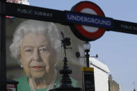 FILE - In this Thursday, April 9, 2020 file photo an image of Britain's Queen Elizabeth II and quotes from her historic television broadcast commenting on the coronavirus pandemic are displayed on a big screen behind the Eros statue and a London underground train station entrance sign at Piccadilly Circus in London. (AP Photo/Kirsty Wigglesworth, File)