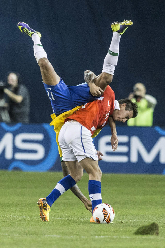 Brazil's Luis Gustavo, left, is upended as he battles for the ball with Chile's Eduardo Vargas during second half action of their international friendly match in Toronto on Tuesday Nov. 19, 2013. (AP Photo/The Canadian Press, Chris Young)