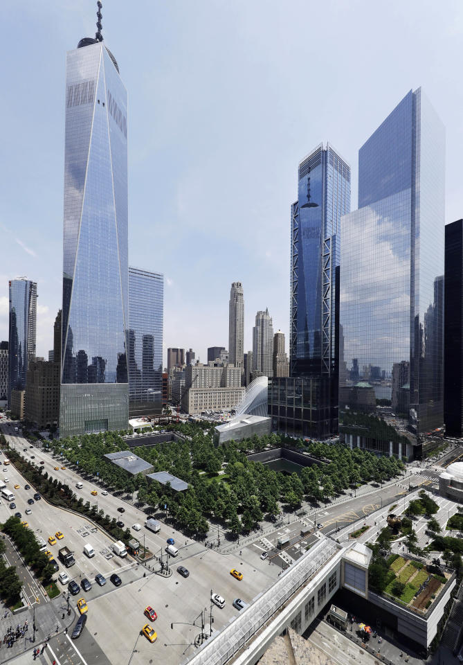 In this June 8, 2018 photo, 3 World Trade Center, second from right, joins its neighbors One World Trade Center, left, and 4 World Trade Center, right, next to the September 11 Memorial and Museum in New York. The center's latest skyscraper opens Monday. (AP Photo/Mark Lennihan)