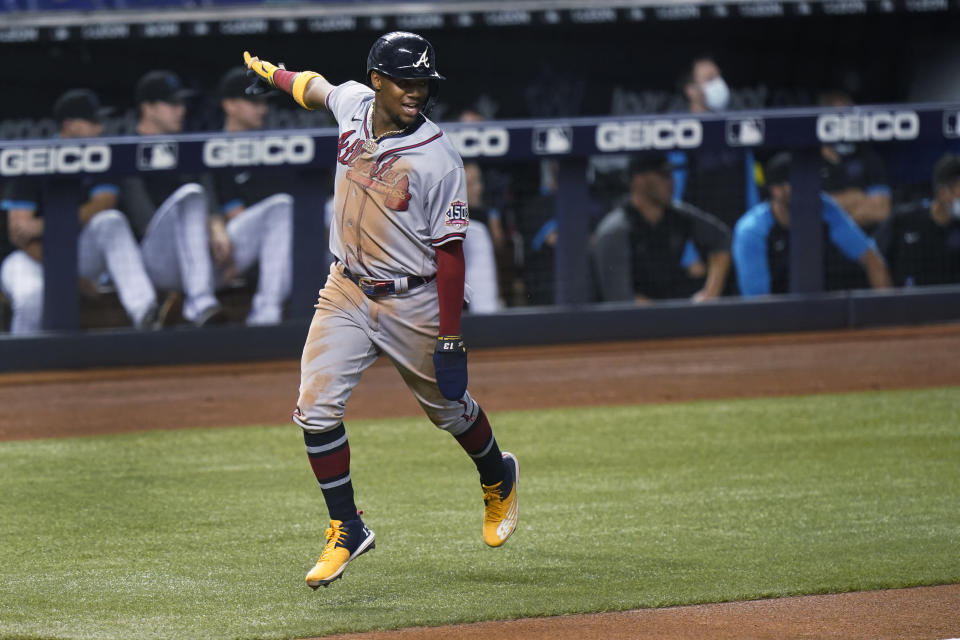 Atlanta Braves' Ronald Acuna Jr. celebrates as he scores on a double by Ozzie Albies during the third inning of the team's baseball game against the Miami Marlins, Friday, June 11, 2021, in Miami. (AP Photo/Wilfredo Lee)