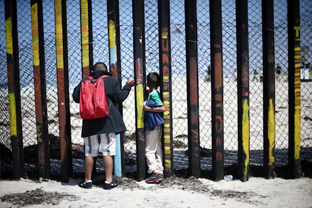 <p>Members of a caravan of migrants from Central America look through the border fence between Mexico and the U.S., prior to preparations for an asylum request in the U.S., in Tijuana, Mexico April 29, 2018. (Photo: Edgard Garrido/Reuters) </p>