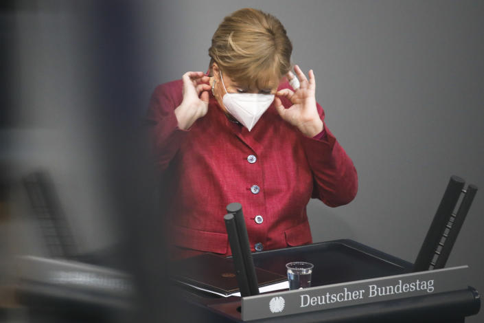 German Chancellor Angela Merkel adjust her face mask after her speech during a parliament session about a new law to battle the coronavirus pandemic at the parliament Bundestag in Berlin, Germany, Friday, April 16, 2021. (AP Photo/Markus Schreiber)