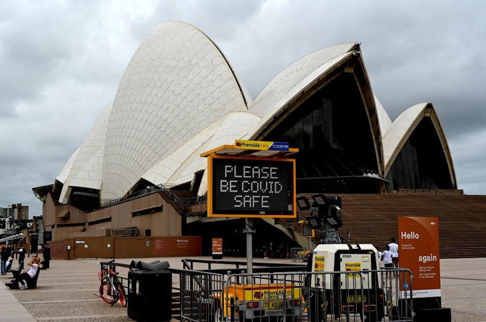 A sign about the Covid-19 coronavirus is displayed at the Sydney Opera House.