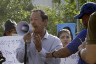 Rong Chhun, center, president of the Cambodian Confederation of Unions uses a megaphone during a protest near the prime minister's residence in Phnom Penh, Cambodia July 29, 2020. Rong Chhun was arrested Friday night, July 31 on a charge of inciting social unrest because of his comments about a politically sensitive matter concerning the country's borders. (AP Photo/Heng Sinith)