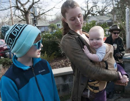 Melissa Orion, 31, holds son Jackson, 8 months, as her other son, Zen Orion-Orchard, 10, watches his younger brother, while in the courtyard of the Ashland Food Cooperative in Ashland, Oregon February 4, 2015. REUTERS/Amanda Loman