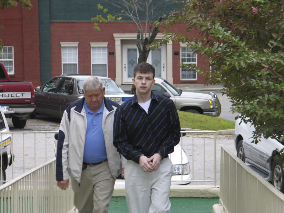 In this Oct. 20, 2006 photo, Evan Miller, right, is escorted to the Lawrence County Courthouse in Moulton, Ala. A judge is set to decide the punishment for the Alabama man, sentenced to life in prison for a murder he committed at age 14, and whose case later led to a ban on mandatory life sentences for juveniles. The judge will decide Tuesday, April 27, 2021 if Evan Miller should be given an opportunity at parole one day or if he should die in prison because of a crime he committed as a teenager. (The Decatur Daily via AP, file)