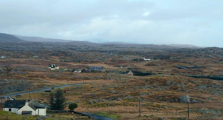 A wet and windswept landscape dotted with homes.