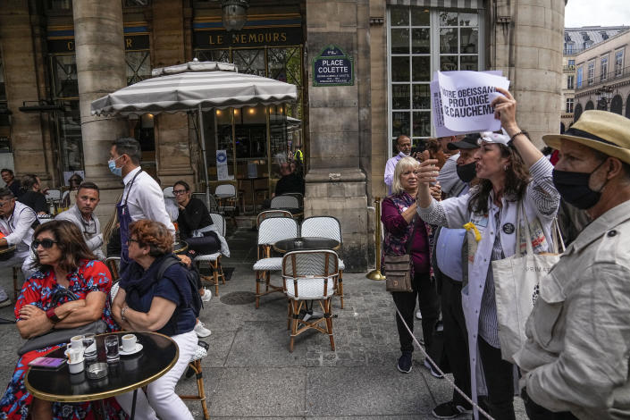 Anti heath pass demonstrators stage a protest next to a cafe terrace outside the Constitutional Council in Paris, Thursday, Aug. 5,2021. France's Constitutional Council is deciding on Thursday whether the health pass that is to open the doors and terraces to cafes, restaurants, trains and hospitals starting next week is in line with the nation's most cherished principles. (AP Photo/Michel Euler)