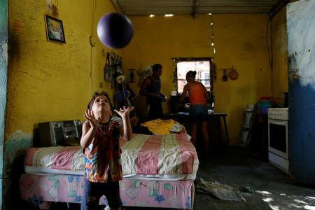 Emmanuel Cuauro, 4, plays with a ball next to his parents Zulay Pulgar (R), 43, and Maikel Cuauro, 30, in their house in Punto Fijo, Venezuela November 17, 2016. Picture taken November 17, 2016. REUTERS/Carlos Garcia Rawlins