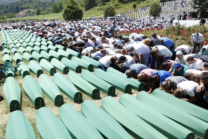 "FILE - A Monday, July 11, 2016 file photo of Bosnian people saying prayers in front of coffins during a funeral ceremony for the 127 victims at the Potocari memorial complex near Srebrenica, 150 kilometers (94 miles) northeast of Sarajevo, Bosnia and Herzegovina. A Bosnian Serb leader has wrongly called the 1995 Srebrenica massacre, where over 8,000 Muslim men and boys were killed by Bosnian Serb troops, ""a fabricated myth."" Milorad Dodik, head of Bosnia's multi-ethnic joint presidency, spoke during a conference discussing war crimes. His comments defy international court rulings that said genocide was committed in the eastern Bosnian enclave and have angered Bosnian Muslims. (AP Photo/Amel Emric, File)"