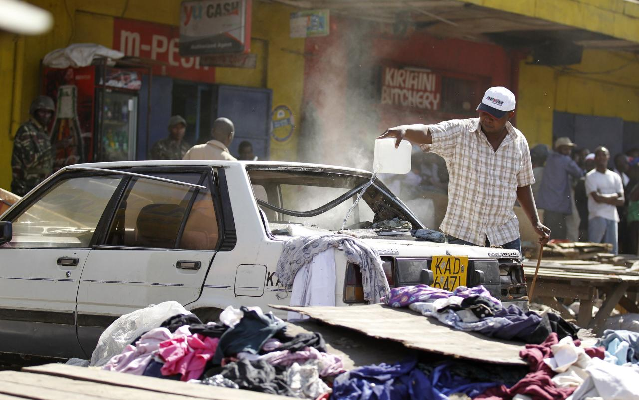 A trader attempts to extinguish fire inside a car at the scene of a twin explosion at the Gikomba open-air market for second hand clothes in Kenya's capital Nairobi May 16, 2014. At least four people were killed on Friday in two explosions in the Kenyan capital Nairobi, the country's National Disaster Operations Centre (NDOC) said. REUTERS/Thomas Mukoya (KENYA - Tags: SOCIETY CIVIL UNREST CRIME LAW DISASTER)