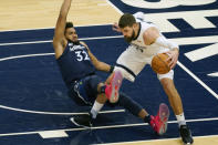 Minnesota Timberwolves' Karl-Anthony Towns, left, falls while getting tangled up with Memphis Grizzlies' Jonas Valanciunas in the first half of an NBA basketball game, Wednesday, Jan. 13, 2021, in Minneapolis. (AP Photo/Jim Mone)