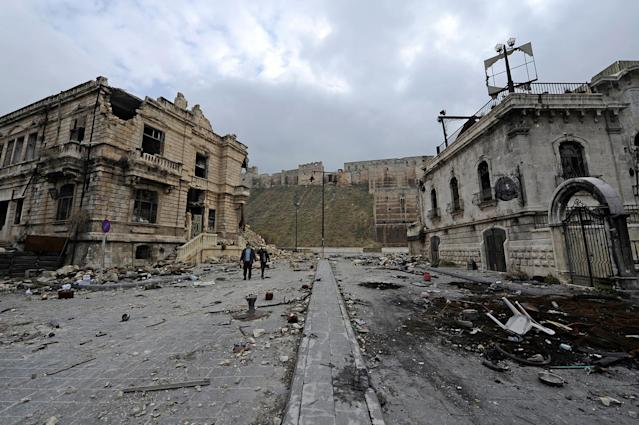 <p>People walk past the old customs buildings (left) and Peoria restaurant (right) near Aleppo's historic citadel, in the government-controlled area of the city, Syria, Dec. 17, 2016. (Photo: Omar Sanadiki/Reuters) </p>